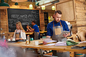 a coffee shop owner checks the delivery notes in his bookkeeping folder on the counter of his busy coffee shop and cross checks them with his online accountancy via his digital tablet. In the background two staff attend to the orders .