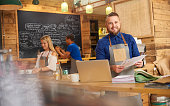 a coffee shop owner checks the delivery notes in his bookkeeping folder on the counter of his busy coffee shop. In the background two staff attend to the orders. The owner takes a moment from his work to smile to camera.