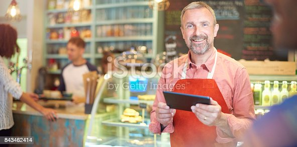 istock coffee shop owner checking his online accounts 843462414