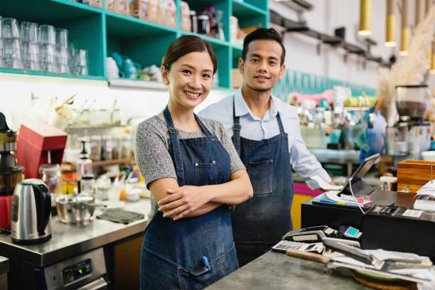Coffee Shop Owner Couple Small Business Malaysia Proud, happy and confident smiling asian Small Business Coffee Shop Owner Couple standing together behind the counter in their stylish cafe in Kuala Lumpur, Malaysia business Malaysia stock pictures, royalty-free photos & images