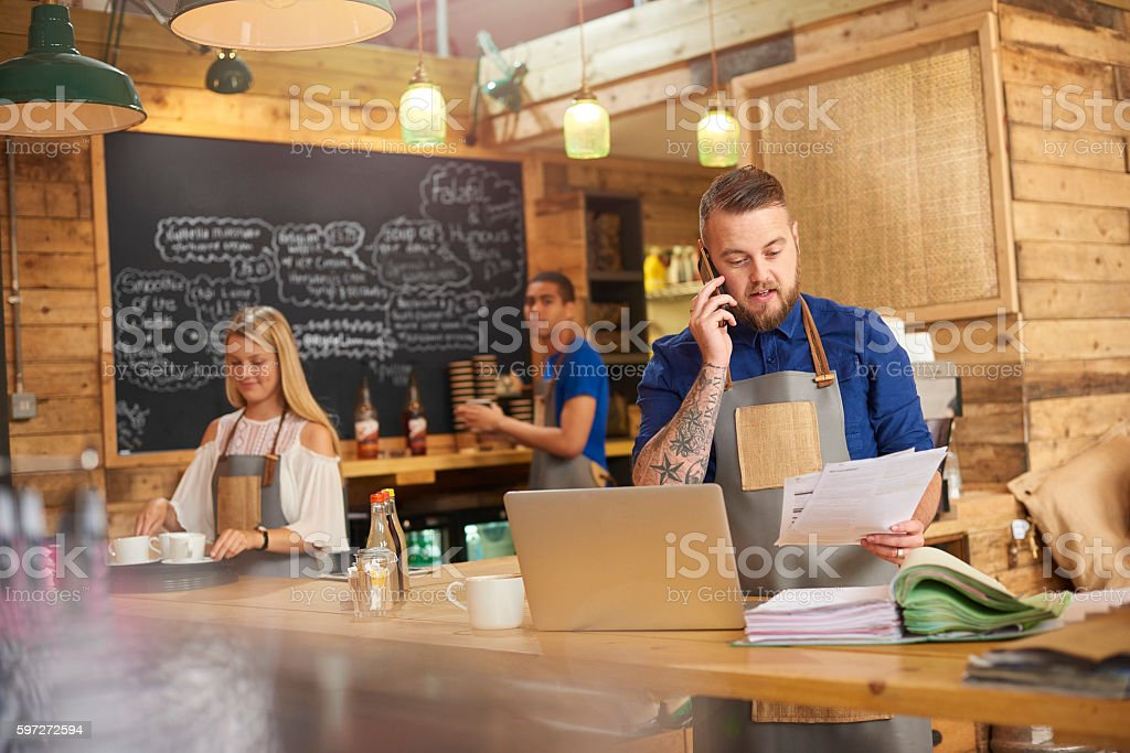Coffee shop owner phoning accountant Lizenzfreies stock-foto