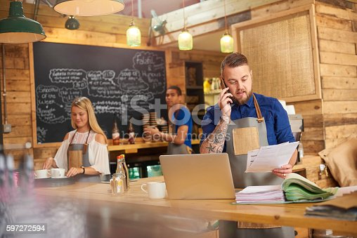 istock Coffee shop owner phoning accountant 597272594