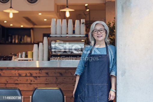 A Taiwanese senior lady wearing an apron standing in a café in Taipei.