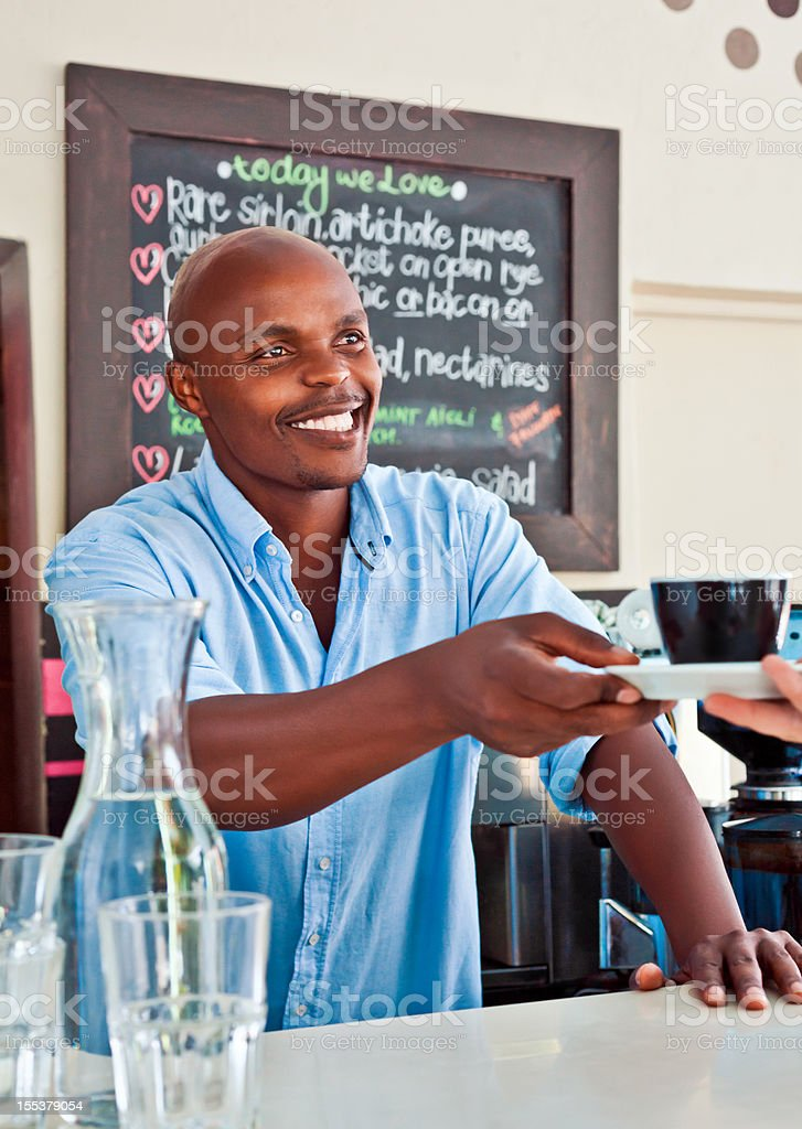 Coffee Shop Owner Friendly african man serving coffee in coffee shop. Adult Stock Photo