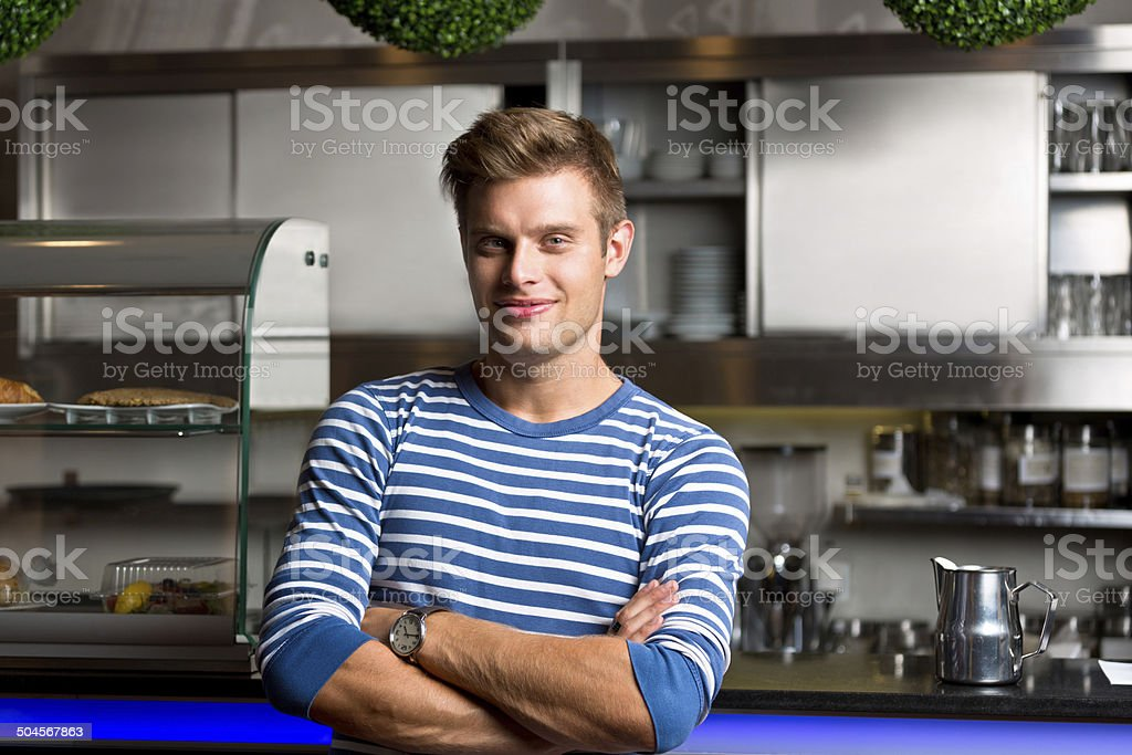 Coffee shop owner Friendly young man standing in front of the bar counter in coffee shop and smiling at camera. 20-24 Years Stock Photo