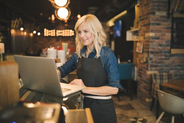 Coffee shop owner working on laptop stock photo