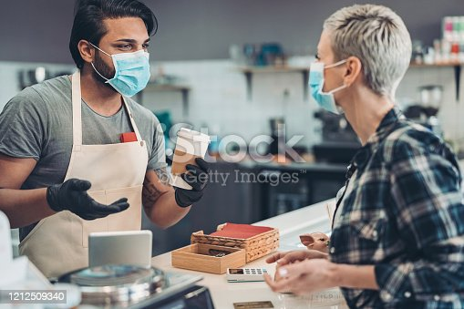 Couple of people with protective masks in cafe