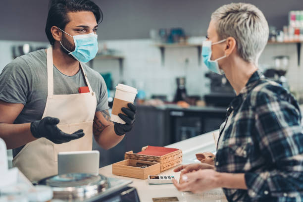 Coffee shop owner working with a face mask and protective gloves stock photo