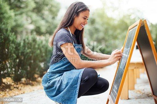 istock Coffee shop owner writing on chalkboard 1060891130