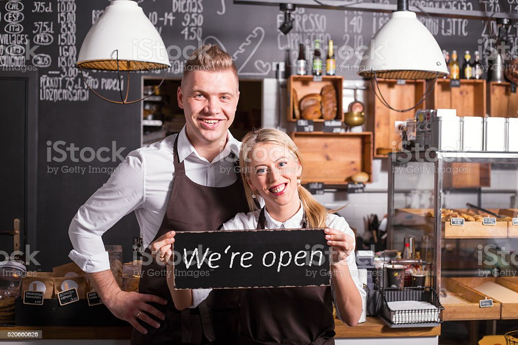 Coffee shop owners showing open sign stock photo