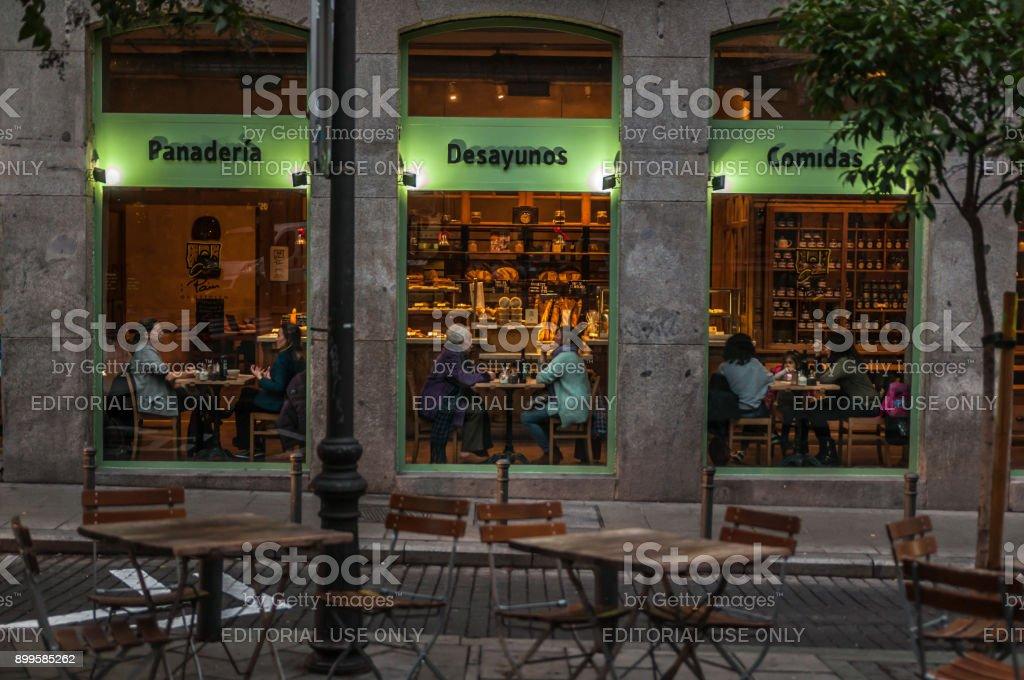 Ventana de la tienda de café con sus mesas llenas de gente. - foto de stock