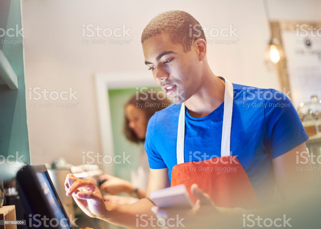 coffee shop worker with digital order screen stock photo