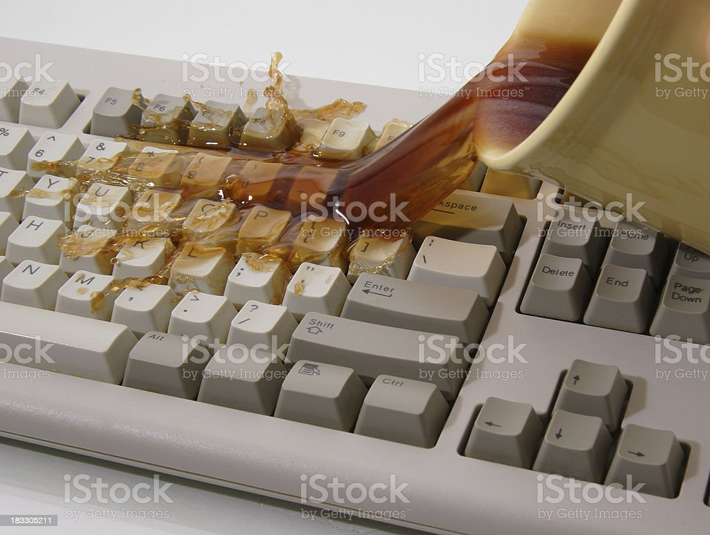 Coffee Spilled on Keyboard A tipped over mug of coffee spills all over a computer keyboard. Accidents and Disasters Stock Photo