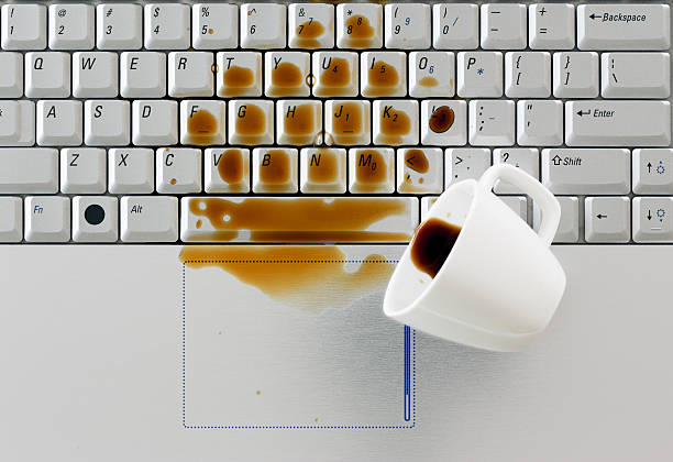 Coffee spilled on keyboard, Coffee spilled on keyboard, close up shot. Damaged computer that needs reparation. Data safety and laptop insurance concept. spilling stock pictures, royalty-free photos & images