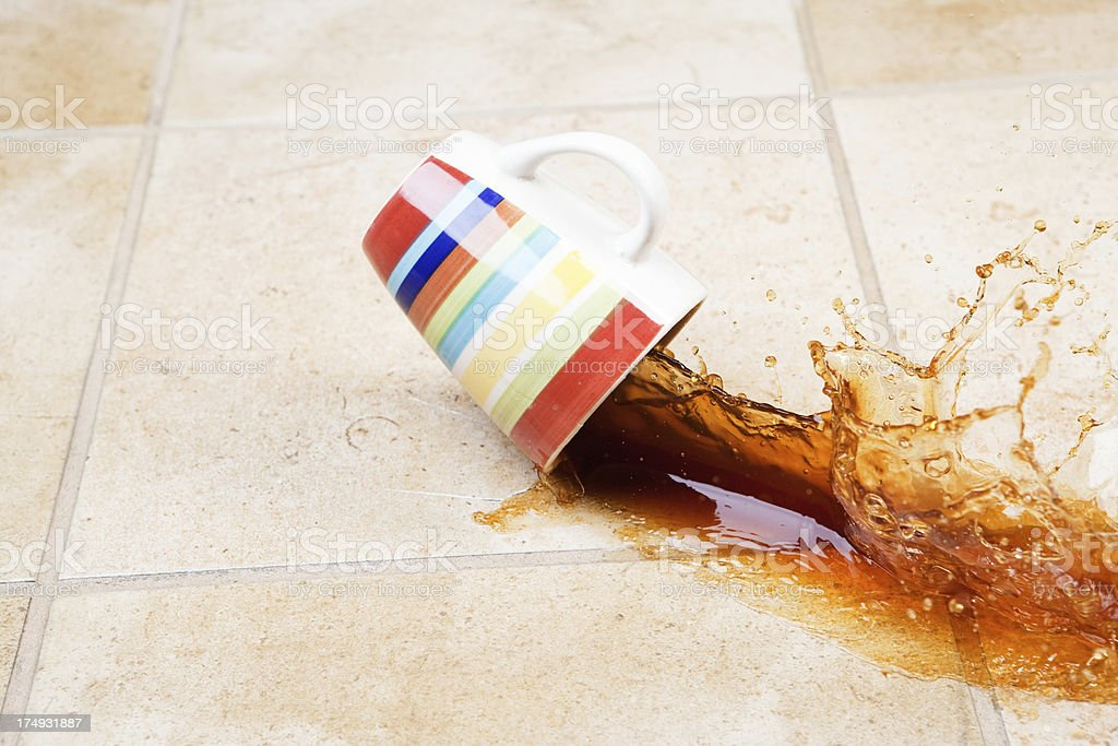 Coffee Spilling from Cup onto Tile Floor stock photo