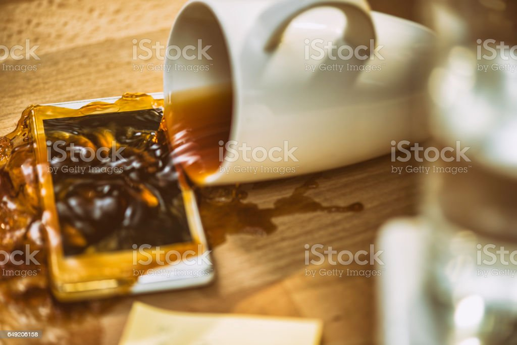 Coffee spilling over smartphone stock photo