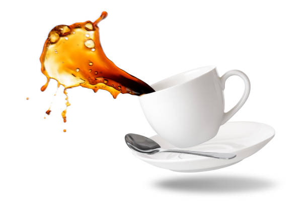 Coffee splashing Black coffee splash out of a cup isolated on white background. spilling stock pictures, royalty-free photos & images