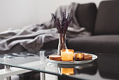 istock Coffee table design idea: aroma candles and dried lavender bouquet on a metal tray, sofa with grey blanket on background. Simple Scandinavian home decor. Hygge concept 1244745891