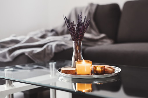 Coffee table design idea: aroma candles and dried lavender bouquet on a metal tray, sofa with grey blanket on background. Simple Scandinavian home decor. Hygge concept