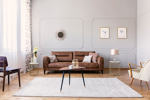 Coffee table with vase and mug in the middle of elegant living room interior with comfortable leather sofa, stylish purple chair and armchair