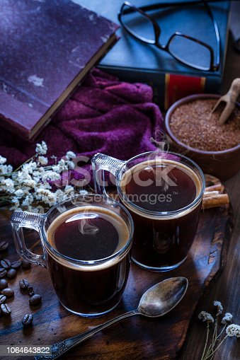 High angle view of two transparent coffee cups placed at the bottom of a rustic wooden table. A vintage metal spoon is in front of the coffee cups. A brown bowl with brown sugar is at the right of the frame. Old books are out of focus at background. Roasted coffee beans, cinnamon sticks and dry flowers bouquet  complete the composition. Predominant color is brown. Low key DSRL studio photo taken with Canon EOS 5D Mk II and Canon EF 100mm f/2.8L Macro IS USM.