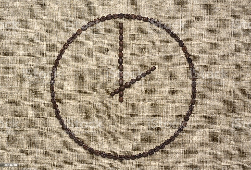 Coffee time concept. Clock of beans on grunge canvas royalty-free stock photo