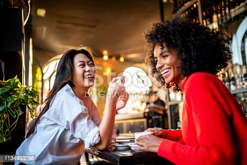 Two smiling female friends having a coffee at the bar