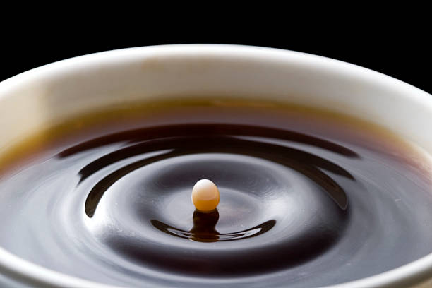 Coffee time A drop of milk falling in a cup of coffee black coffee stock pictures, royalty-free photos & images