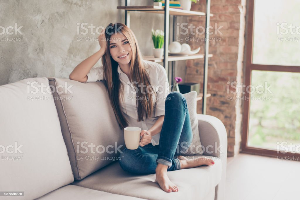 Coffee time. Smiling happy charming young lady on the couch at home having coffee and relaxing, so cozy and comfortable stock photo