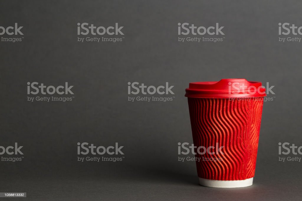 coffee to go in a disposable cup on a black background, place for text