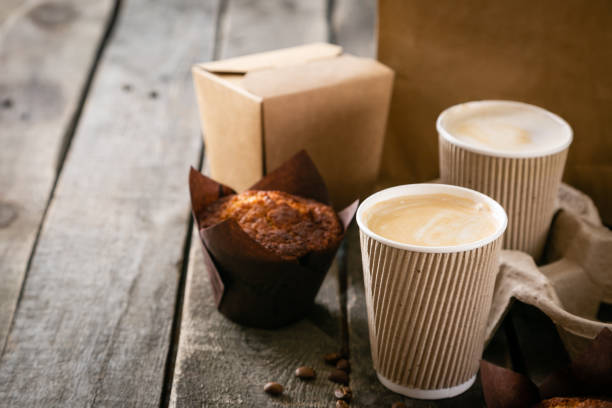 Coffee to go with muffin on wood background