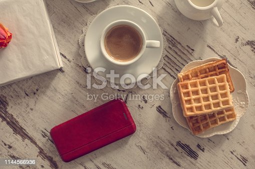 Coffee, waffles, smart phone and book on the wooden table, directly above.