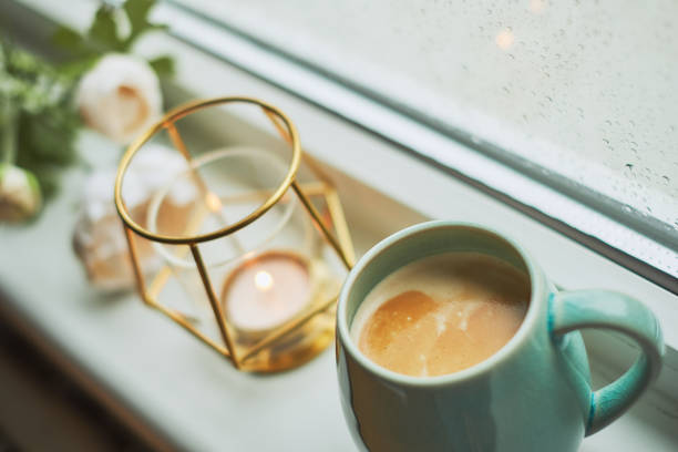 Coffee with amaretto biscuits on a window sill stock photo