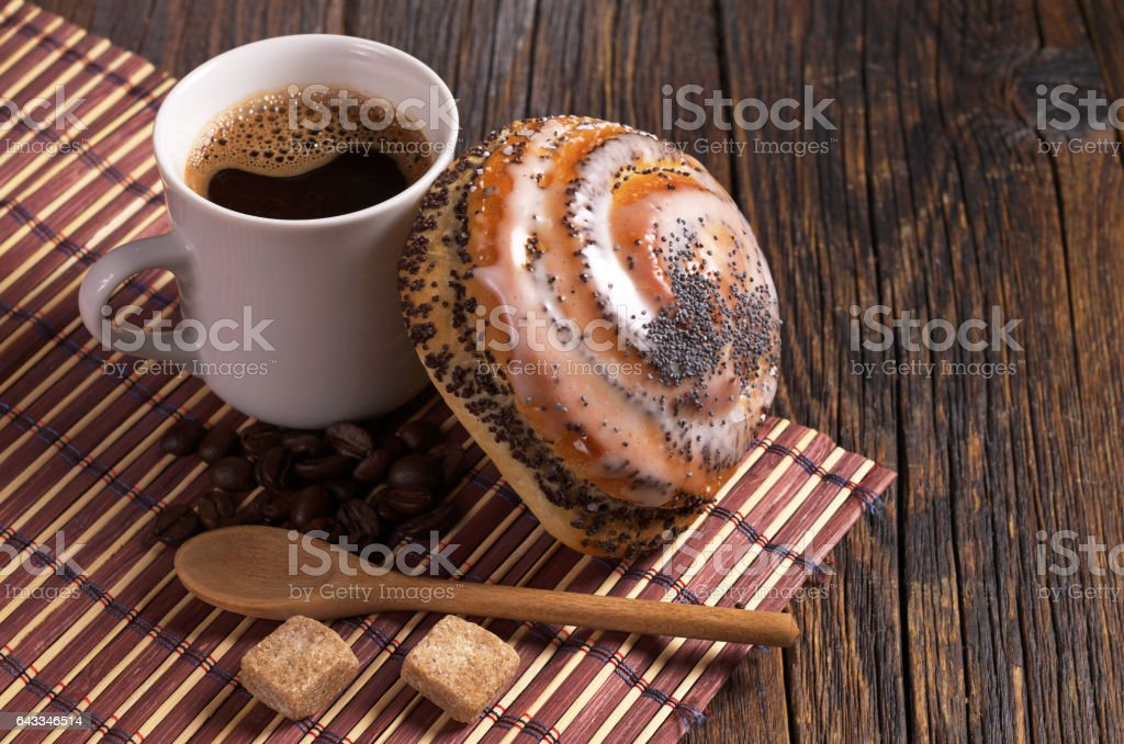 Cup of coffee and fresh bun with poppy seeds on dark wooden table