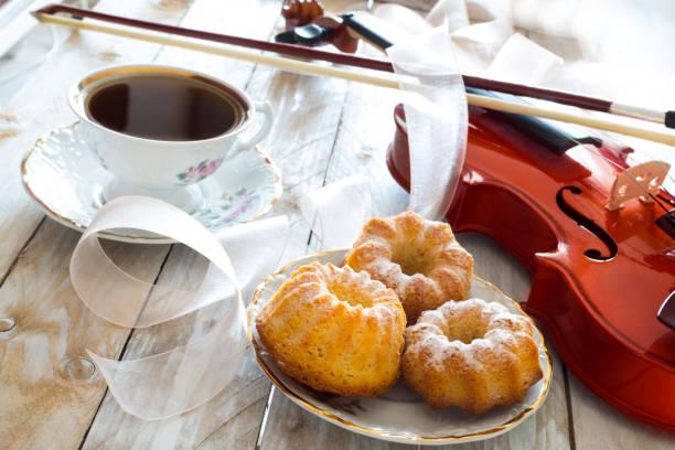 kaffee mit muffins und violine auf dem holztisch - musik kuchen stock-fotos und bilder