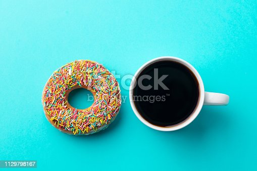 Coffee with donut on blue background. Top view