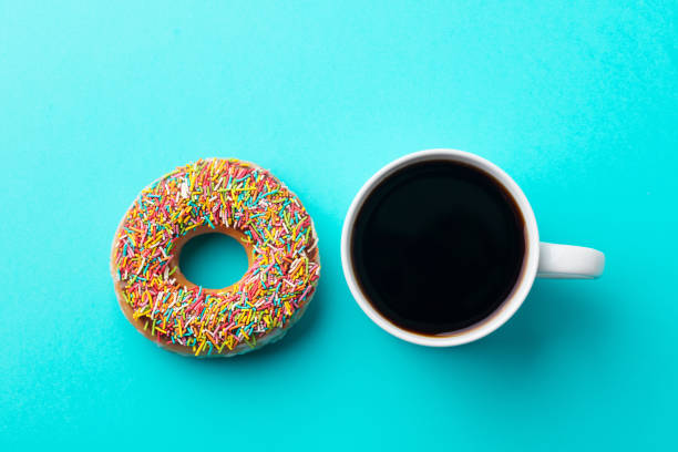 coffee with donut on blue background. top view. - bombolone foto e immagini stock
