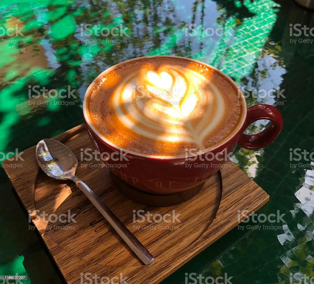 Coffee with flower shaped foam on green marble table in outdoor...