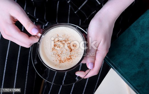 istock Coffee with foam and cinnamon in woman hands 1252412986