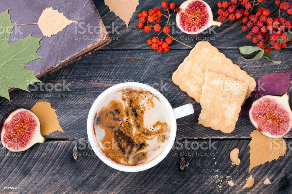 Coffee with foam, cookies, figs, old book, autumn leaves and dried rowan on wooden background. Concept cozy atmosphere with a cup of coffee. Autumn card stock photo