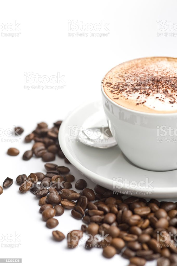 Coffee with foam in a white cup on saucer with coffee beans royalty-free stock photo