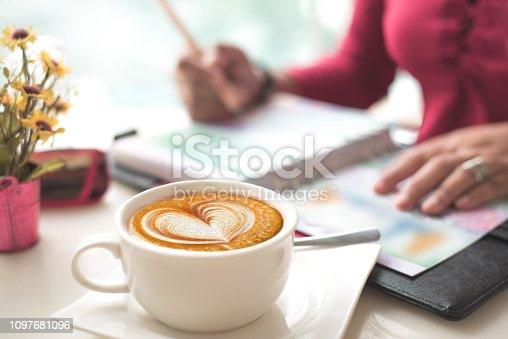 istock Coffee with Heart Shape Latte Art on Working Desk 1097681096