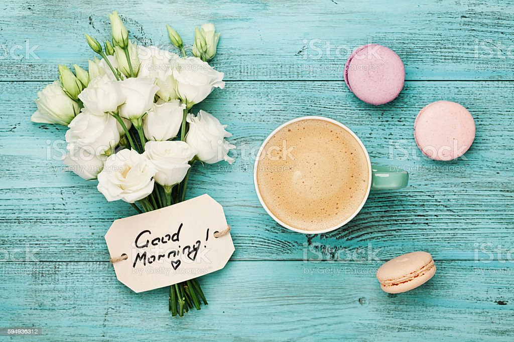 Coffee with macaron, flowers and notes good morning. Flat lay. stock photo
