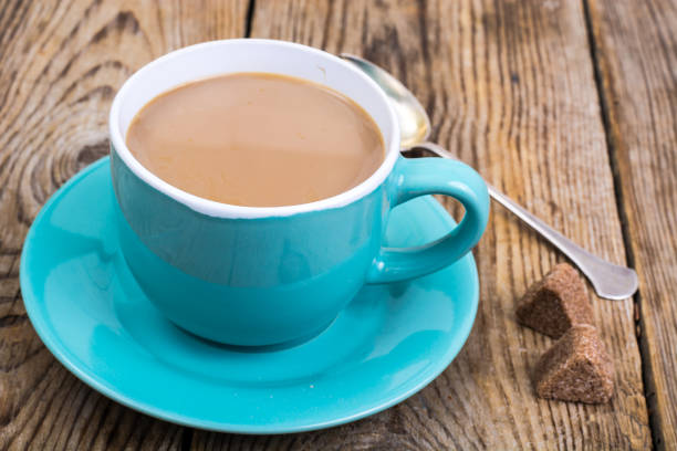 Coffee with milk in blue cup, pieces of sugar stock photo