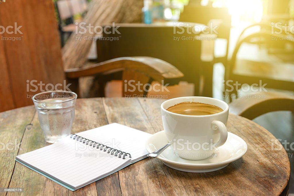 Coffee with notebook and water glass on wooden table. royalty-free stock photo