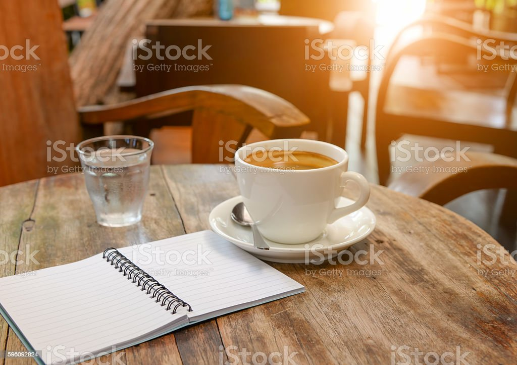 Coffee with notebook and water glass on wooden table. Lizenzfreies stock-foto