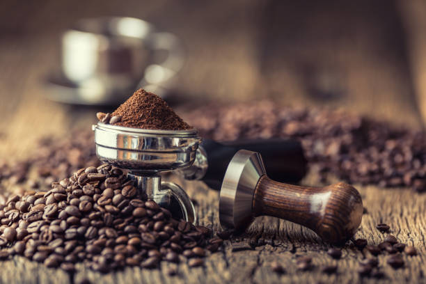 Coffee.Coffee beans and portafilter on old oak wooden table Coffee.Coffee beans and portafilter on old oak wooden table. caffeine stock pictures, royalty-free photos & images