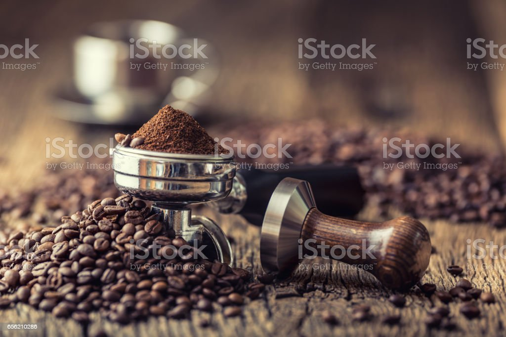 Coffee.Coffee beans and portafilter on old oak wooden table stock photo