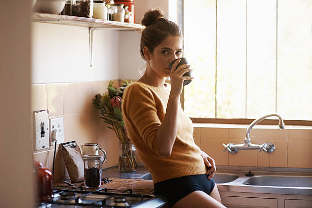 Coffee-fuelled morning thoughts Shot of a beautiful young woman enjoying a warm drink in the kitchenhttp://195.154.178.81/DATA/i_collage/pi/shoots/783580.jpg panties stock pictures, royalty-free photos & images
