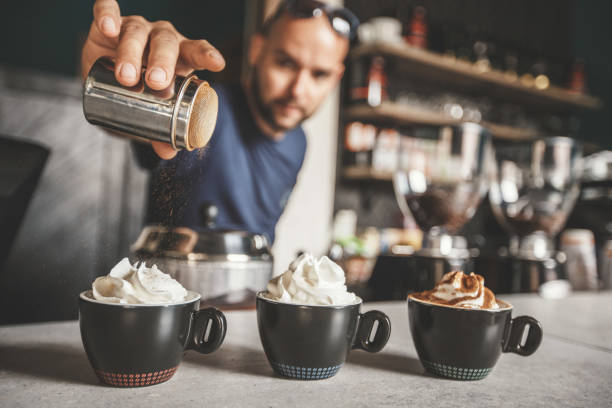 Coffees with different flavours Barista is spreading cinnamon on a coffee with whipped cream. Except the simple coffee with whipped cream, he is making coffee with extra cinnamon and cocoa powder. barista stock pictures, royalty-free photos & images